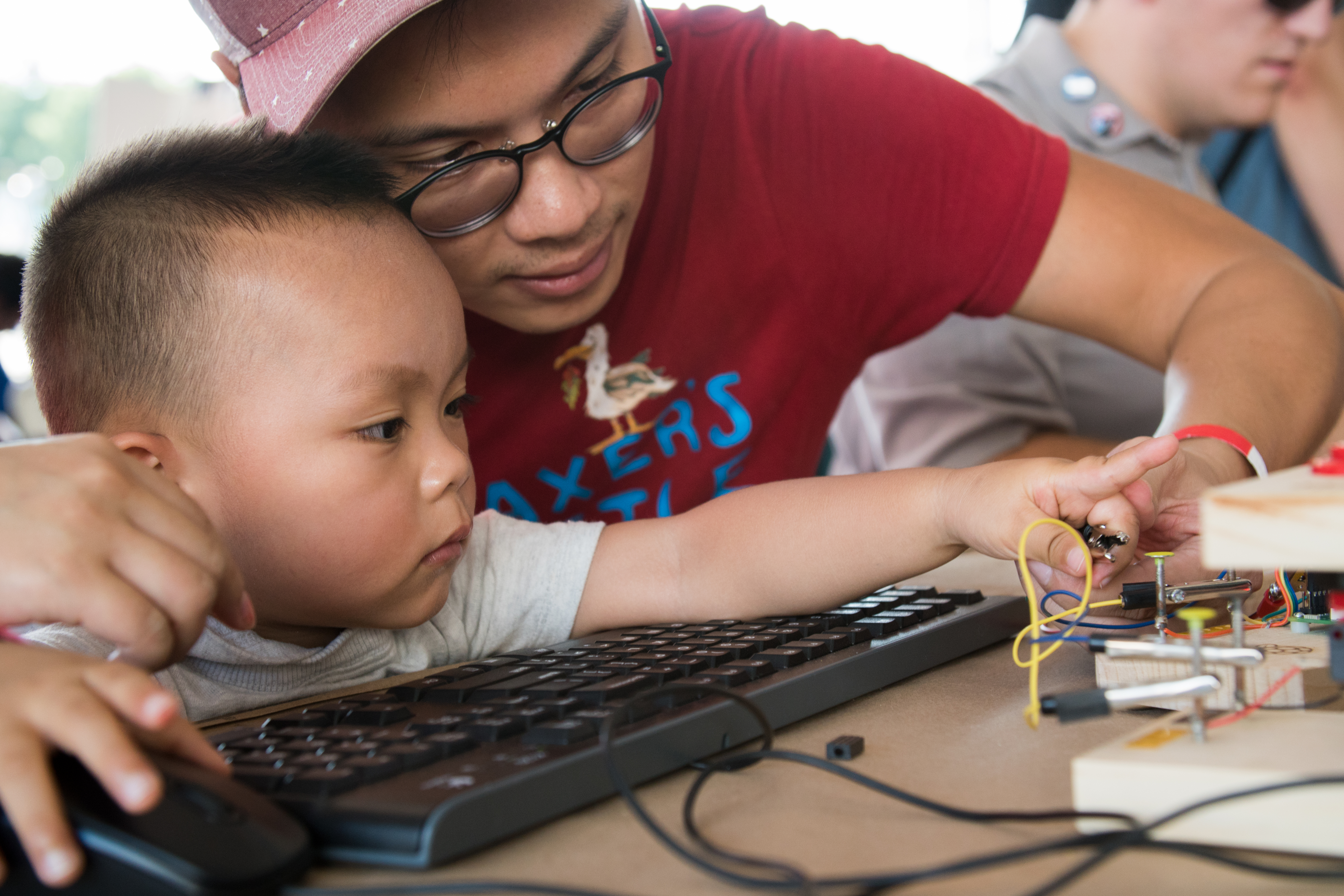 Father and infant child clip crocodile leads to the Raspberry Pi physical computing blocks at Maker Faire New York